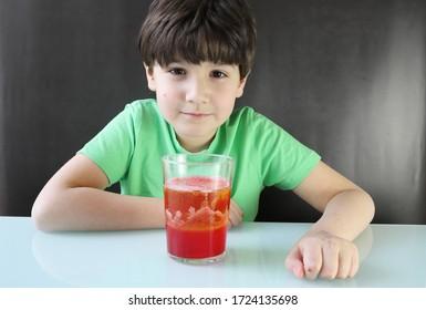 Kind, das ein Experiment durchführt, eine Lavalampe mit Wasser, Öl, Farbe und Brausetablette