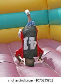 Child doing head stands inside air filled play area