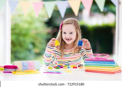 Child doing homework for school at white desk. Wooden educational abc toy puzzle for kids. Happy back to school student. Kid learning alphabet letters. Little girl with school supplies and books.