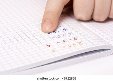 child doing maths homework, adding numbers