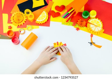 The child is doing paper craft lion the workshop. An animal from hot Africa. Children's hand. Material for creativity. White background.