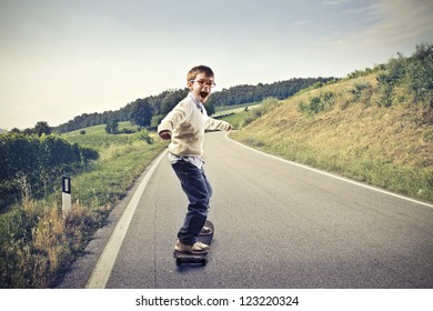 Child doing skateboard on a long road