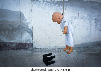 Child doll execute hanging with chair beside the wall. Children doll commit suicide concept. kid kill oneself with rope and chair background
