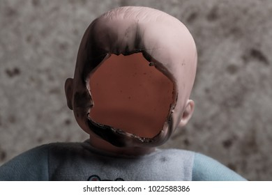 Child Doll with Its Face Cutted Off and Burned on Grunge Background