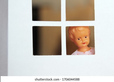 A child doll in the window, girl looking outside from home. Toy representation of confinement, self-isolation,social distancing during coronavirus crisis and Covid-19 pandemic, children stay at home.