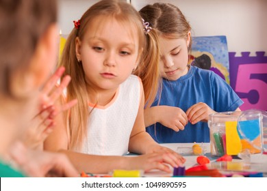 Child dough play in school. Plasticine for children. mold from plasticine in kindergarten. Kids knead modeling clay with hands in preschool. Zoo from plasticine. Preparation for origami exhibition.