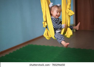 child with Down syndrome is engaged in yoga, a yellow hammock and the atmosphere of a children's center, a concept childhood