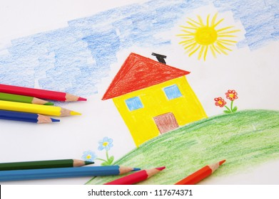 A child draw with an house  and flowers with colorful pencils