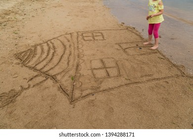 the child draw house picture on the sand at the beach by the sea in the summer for holiday concept.