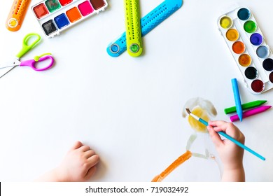 The child is drawing with a brush with acrylic paints on a blank sheet of white paper. Kid is drawing with watercolors