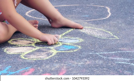 The child drawing a chalk on asphalt. Child drawings paintings on asphalt concept.