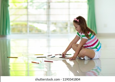 Child drawing with colorful pencil sitting crisscross on white tiles floor at home. Kid painting and doing art homework after school. Children draw and paint. Kids room with big window.