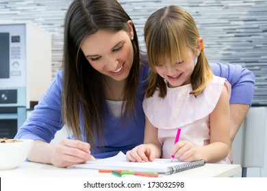 Child drawing with crayons with her mom, sitting at table in kitchen at home