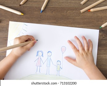 Child drawing happy family on paper. Top View