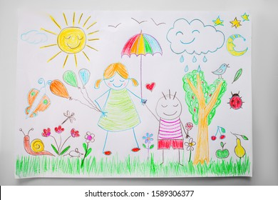 Child drawing a happy family in a park with color pencils.