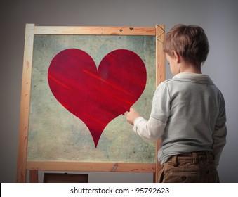 Child drawing a heart on a blackboard