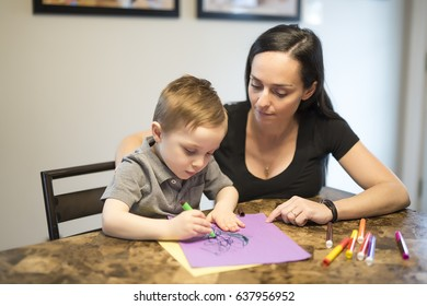 A Child drawing with his mom, sitting at table in kitchen at home