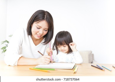 Child drawing with mother