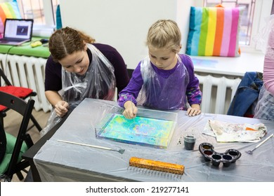 Child drawing with needle on the water. Ebru art is a method of aqueous surface design