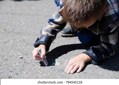 Child drawing on asphalt in spring, child paint crayons in the park