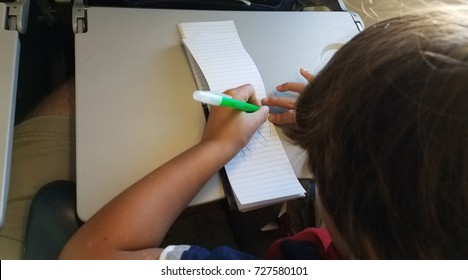 a child drawing on paper while on an airplane