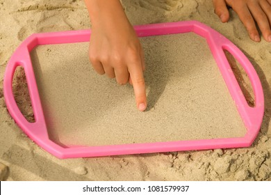 A child is drawing a pattern in sand