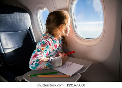 Child drawing picture with crayons in airplane. Little girl occupied while flying in aircraft. Travel with family and kids. Blue sky and sun outside the window