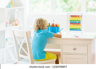 Child drawing rainbow. Kid painting at home. Little boy doing homework after school. Kids desk with abacus in white sunny bedroom. Children study, learn to read and write. Bedroom for student