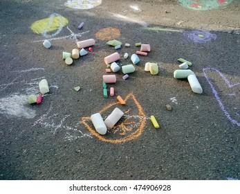 Child drawings on grey asphalt concrete.