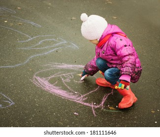 Child draws with chalk on the playground.
