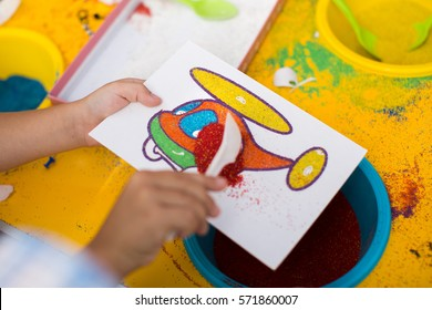 A child draws with colored sand picture. Cartoon characters.