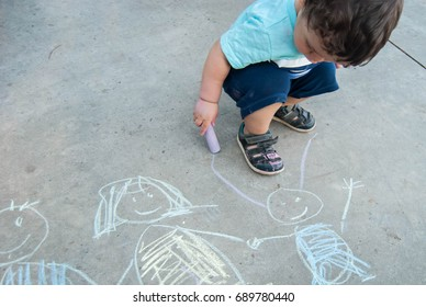 A child draws a family with chalk