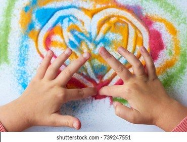 A child draws a heart with colored sand