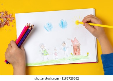 The child draws his family on a piece of paper with colored pencils. My happy family. The concept of child psychology.