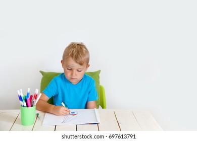 A child draws a house and a cat with colored pencils. Sits by the table. Against the white wall.