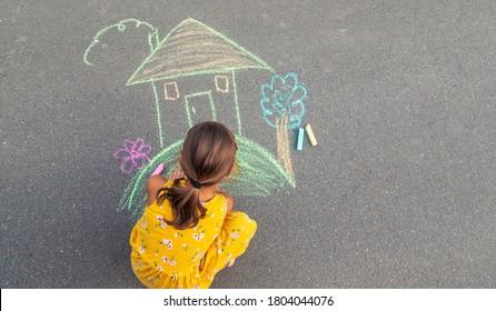 Das Kind zeichnet ein Haus auf dem Asphalt. Selektiver Fokus. Kind.