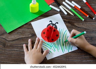Child draws items on a paper card. The child makes a postcard with ladybird. Glue, paper, scissors on a wooden table. Children's art project, a craft for children.