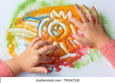 A child draws a man with colored sand on a white sheet