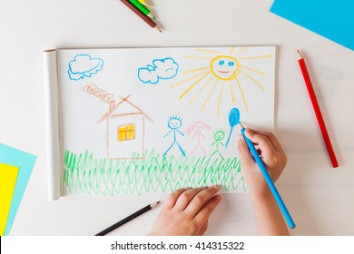 Child draws a pencil drawing of the house and his family. New home. Top view.