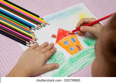 Child draws a pencil drawing of the peace. Green field, the bushes and the house.