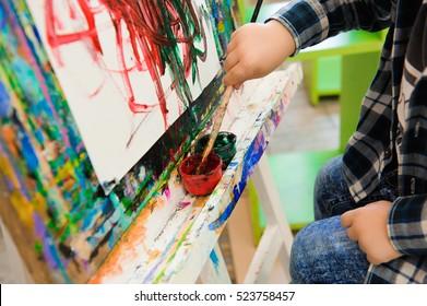 a child draws a picture paints on art lesson.