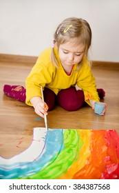 child draws a rainbow