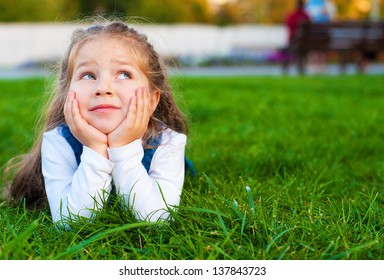 child dreaming on green grass