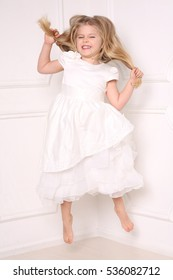 Child in dress jumping and holding her hair. White background