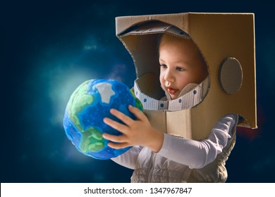 Child is dressed in an astronaut costume. Kid with globe. Earth day.
