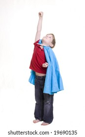 A child dressed in a cape with his hand in the air