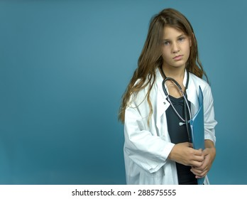 child dressed as doctor with stethoscope and file against a blue background. Concept of not being happy with high expectations of parents.