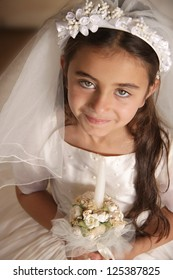 Child dressed up for her first communion with white dress and veil