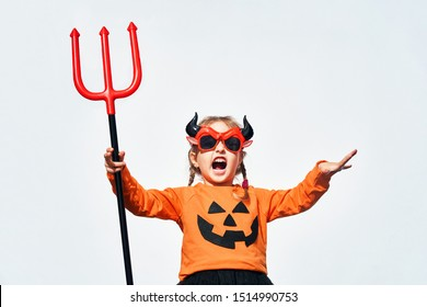a child dressed in orange with a Halloween pumpkin smile, with a red pitchfork in his hands in the image of the devil scares at the Halloween party. child dressed in Halloween costume
