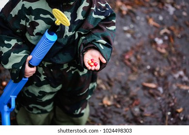 A child dressed in a paintball uniform holds colored bullets in his hand.